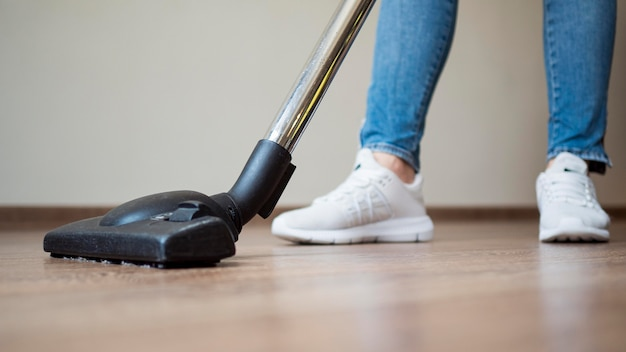 Close-up individual using vacuum cleaner