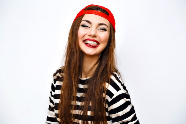 Close up ritratto di stile di vita di moda al coperto di fresca bella giovane donna bruna, capelli lunghi incredibili, trucco luminoso, cappello rosso e maglietta a righe, grande sorriso incredibile, viso carino, immagine urbana con flash.