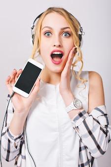 Chiudere l'immagine interna di allegra giovane donna carina ascoltando musica in cuffia, tenendo il telefono cellulare, guardando con occhi sorpresi, toccando il viso. indossare abiti casual alla moda.