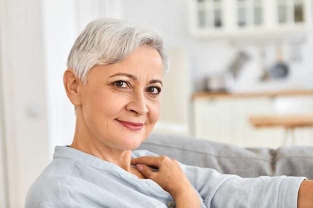 귀여운 매력적인 미소로 아늑한 면화 목욕 가운을 입고 샤워 후 소파에 편안하게 앉아 집에서 휴식을 취하는 우아한 노인 여성 연금의 실내 사진을 닫습니다