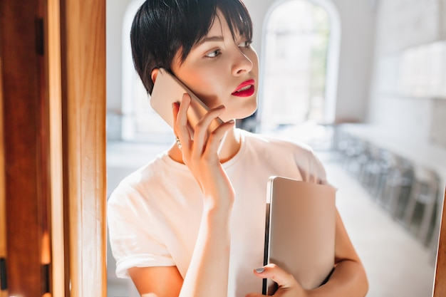 Close-up indoor portrait of busy young woman with red lips and trendy short hairstyle talking on phone