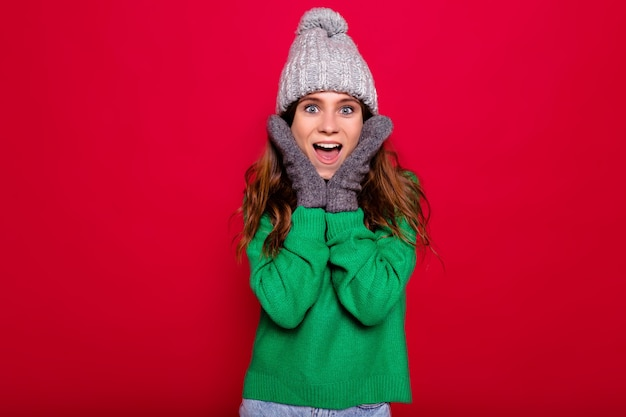 Close up indoor portrait of effective stylish pretty woman with long hair dressed winter cap and green sweatre with surprised emotions on isolated red background