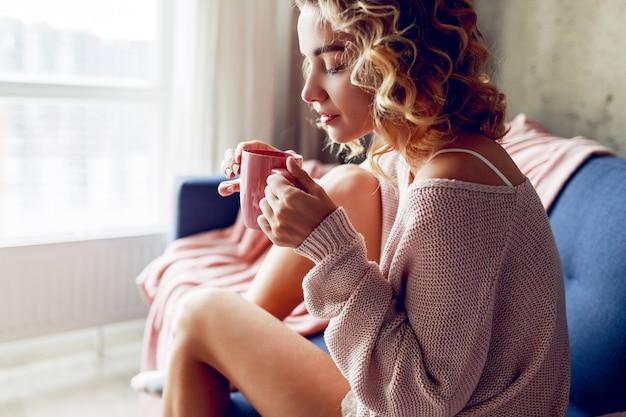 Chiuda sul ritratto dell'interno della donna bionda graziosa che gode dell'odore del cappuccino, sognando e guardando nella finestra. indossare un maglione lavorato a maglia rosa.