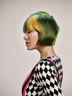 Close-up indoor portrait of lovely girl with colorful hair. studio shot of graceful young woman with stylish short haircut on studio background.