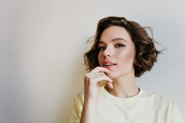 Close-up indoor ritratto di bella ragazza con i capelli scuri. graziosa giovane donna pallida con taglio di capelli corto isolato sul muro bianco.