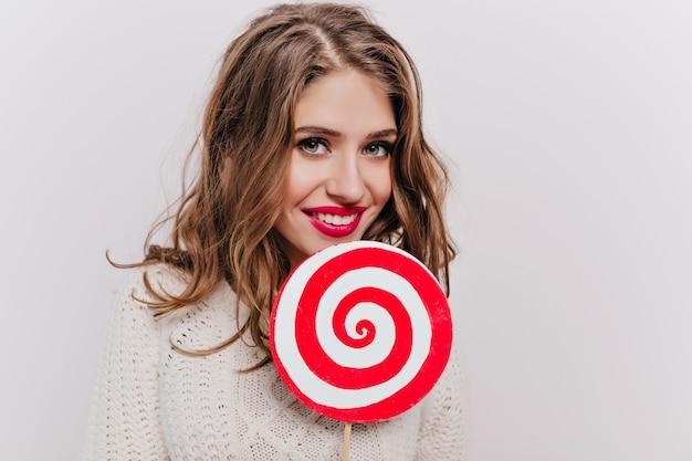 大きな砂糖菓子を持っている茶色の髪の女性のクローズアップ屋内肖像画。光の壁に分離されたロリポップでポーズをとってセーターの壮大な白人の女の子