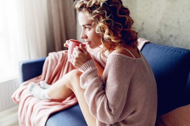 カプチーノの香りを楽しんで、夢を見て、窓を見る優雅なブロンドの女性の屋内ポートレートを閉じます。ピンクのニットセーターを着ています。