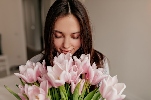닫힌 된 눈과 꽃을 들고 행복 한 미소와 함께 포즈를 취하는 검은 머리와 함께 행복 한 여자의 실내 초상화를 닫습니다.