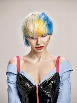 ブロンドの髪を持つ素敵な女の子のクローズアップ屋内肖像画。青い背景にスタイリッシュな短いヘアカットと優雅な若い女性のスタジオショット。