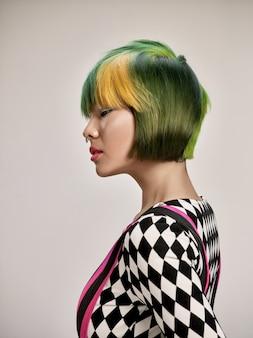 カラフルな髪の素敵な女の子のクローズアップ屋内肖像画。スタジオの背景にスタイリッシュな短いヘアカットを持つ優雅な若い女性のスタジオショット。