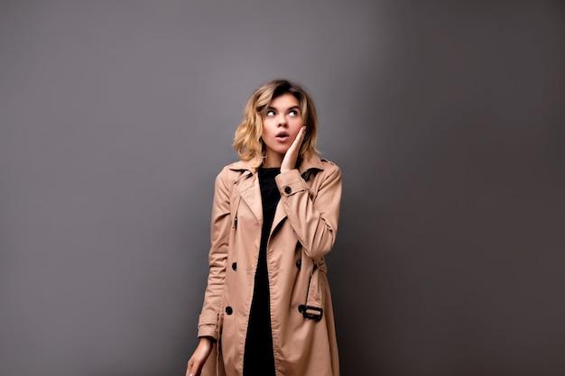 짧은 금발 헤어 스타일으로 사랑스러운 여자의 클로즈업 실내 초상화는 회색 절연 위에 서있는 베이지 색 코트를 입고. 짧은 머리와 우아한 창백한 젊은 여자