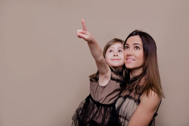 격리 된 벽에 포즈를 취하는 그녀의 작은 매력적인 딸과 함께 젊은 어머니의 실내 초상화를 닫습니다