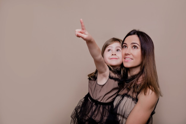 Close up indoor portrait of young mother with her little charming daughter posing on isolated wall