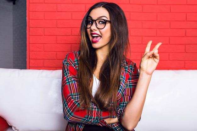 Chiuda sul ritratto dell'interno di giovane donna graziosa dei pantaloni a vita bassa con i capelli lunghi del brunette e trucco luminoso