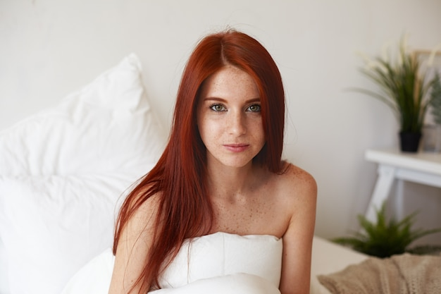 Close up indoor shot of gorgeous young caucasian red haired female with freckled shoulders posing in bedroom