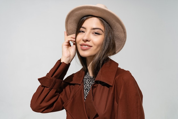 Close up indoor studio fashion portrait of gorgeous woman in stylish winter  brown coat and black hat