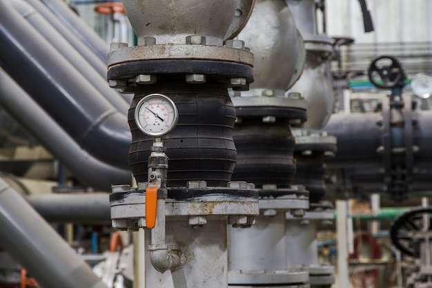 Close up of industrial pipes and measurer of compression, pressure gauge