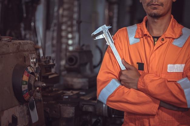 クローズアップの産業労働者、安全服の着用、ノギスの使用、測定器、産業プラントで働く物体の制御
