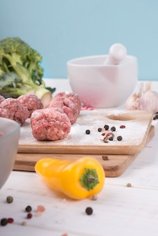 Ингредиенты крупным планом и фрикадельки на деревянной доске
