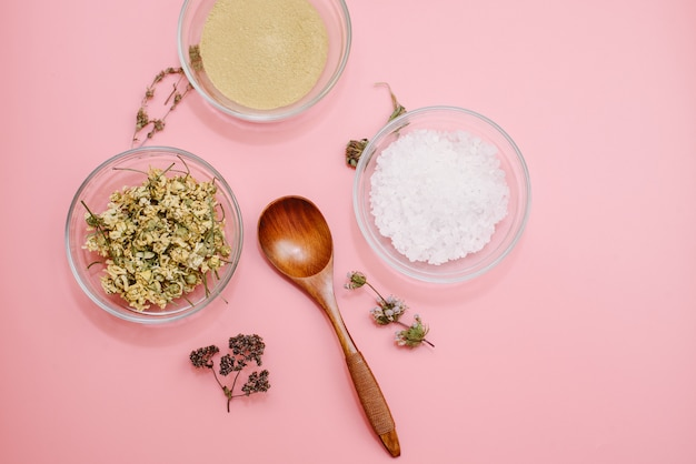 Close up of ingredients of ayurvedic treatment or face pack. yellow clay, turmeric powder and dried chamomile, sea coarse salt in glass cups on a pink pastel colour surface. flat lay blog style