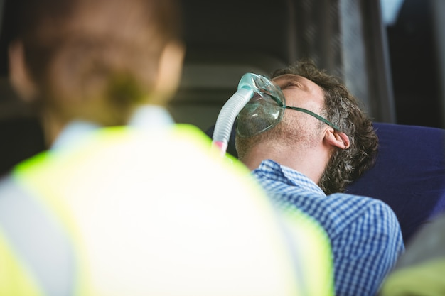 Close-up of an injured man wearing oxygen mask