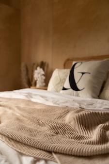 Закройте вверх чернилами пушистую кровать бегунка с кроватью изголовья из ротанга и мягкой подушкой и украшением с фанерной стеной