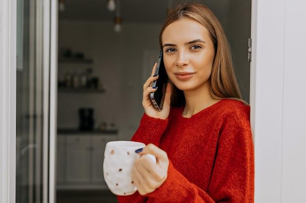 Chiuda in su all'interno del ritratto di signora allegra in maglione rosso che tiene una tazza e parla al telefono in cucina
