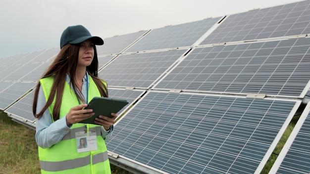 디지털 태블릿 pc와 태양 전지 패널 설치를 확인하는 재생 에너지 역에 검사관 엔지니어 여성을 닫습니다. 태양광 패널 분야. 청정 에너지 생산.
