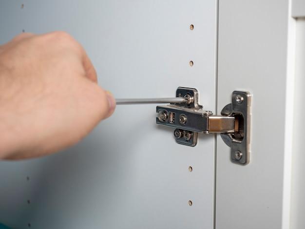 Монтаж мебельных дверей крупным планом с помощью отвертки, концепция сборки мебели. выборочный фокус