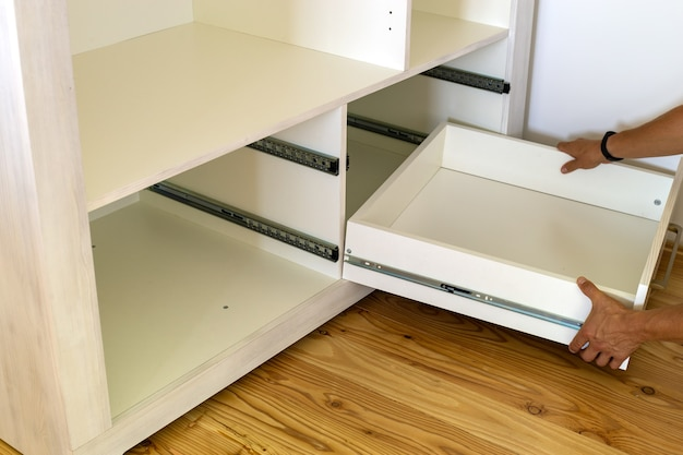 Close up of installation of wooden drawer in contemporary cupboard cabinet.