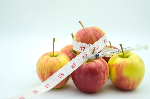 Close up of insulin syringe on fresh apple and tape measure isolated