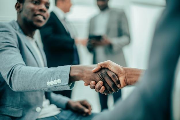 閉じる。お互いに握手する国際的なビジネスの同僚