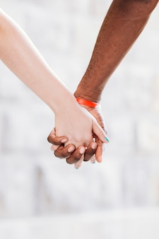 Close-up of interracial couple holding hands