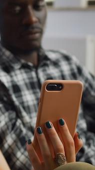 Primo piano di una coppia interrazziale che guarda lo smartphone