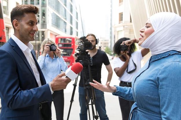 Primo piano sull'intervistato con il microfono che prende dichiarazioni