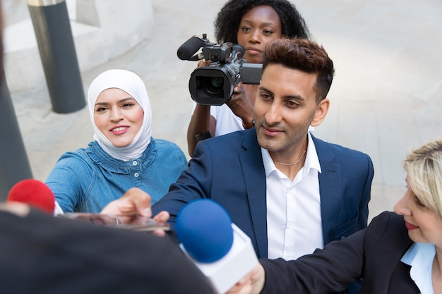 Close up on interviewee with microphone taking statements