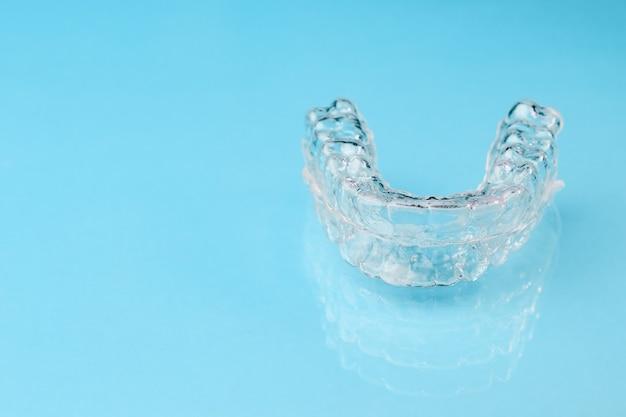 복사 공간이 파란색 배경에 보이지 않는 aligners를 닫습니다. 플라스틱은 치아를 곧게 펴기 위해 치과 용 리테이너를 교정합니다.