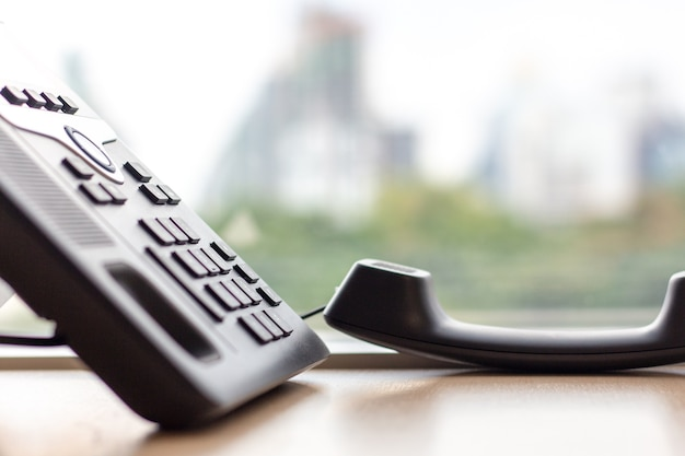 Close up ip phone for office on the table desk with window city view