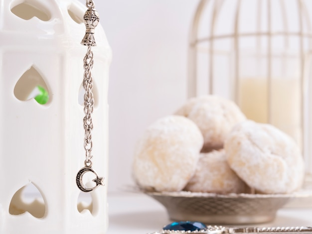 Close up islamic charm with blurred pastries in the background