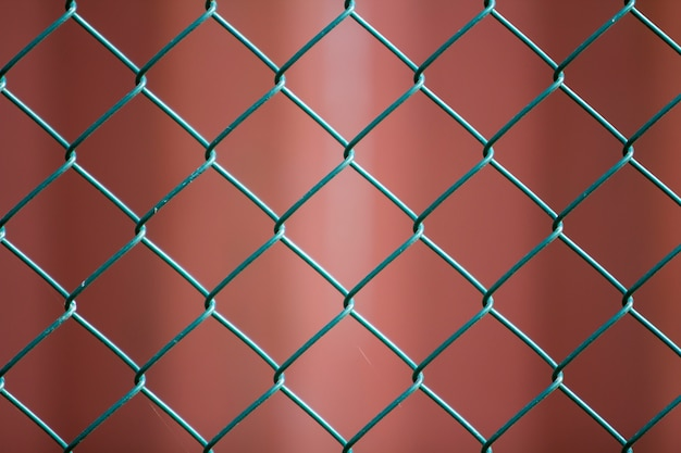 Close-up of isolated painted simple geometric black iron metal wire chain link fence eon dark red. fence, protection and enclosure concept.
