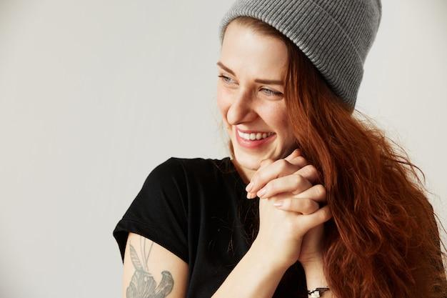Крупным планом изолированный портрет счастливой молодой женщины с длинными рыжими волосами и голубыми глазами