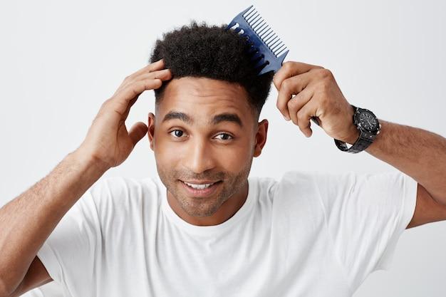 幸せでリラックスした表情でカメラで探している髪をとかす白いスタイリッシュなtシャツの髪をとかして黒い巻き毛の成熟した浅黒い魅力的な男性大学生の孤立した肖像画を閉じる