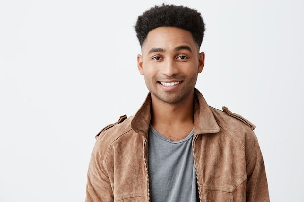 Close up isolated portrait of young dark-skinned attractive guy with afro hairstyle in grey t-shirt under brown jacket smiling with teeth looking in camera with happy and peaceful face expression.