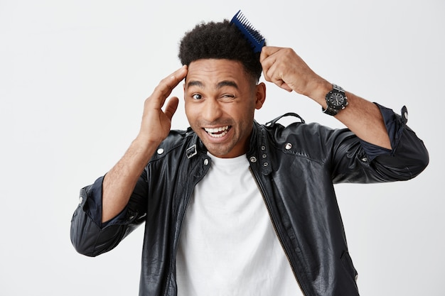 Close up isolated portrait of young funny dark-skinned attractive men with curly hair in fashionable outfit combing hair, getting ready for a walk, making silly faces.