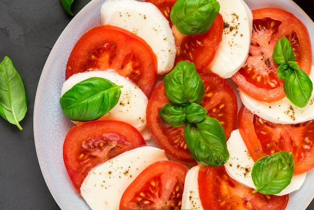Close up of italian caprese salad with sliced tomatoes, mozzarella cheese, basil, olive oil, pepper in a plate
