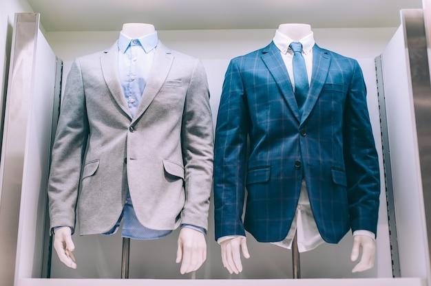 확대. 재킷 셔츠와 넥타이가 상점 창에 매달려 있습니다.