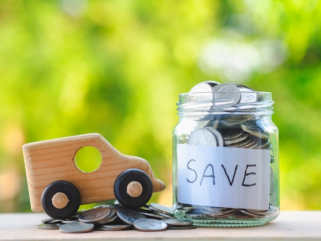 Close up jar of coins and toy car on wooden table on blur background