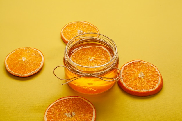 Close-up jar with honey and tasty orange slices