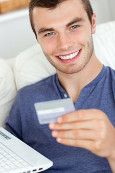 Close up of a jolly man holding a card and a laptop
