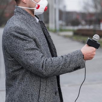 マスクを持つジャーナリストのクローズアップ男